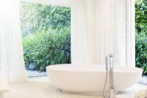 Bathtub, curtain, and windows in modern bathroom — Stock Photo