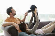 Couple relaxing with dog on sofa at modern home — Stock Photo