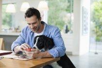 Hombre alimentación perro en cocina mesa - foto de stock