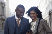 Smiling business people text messaging with cell phone — Stockfoto
