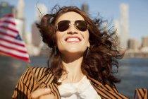 Smiling woman waving American flag — Stock Photo