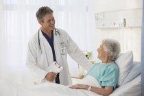 Доктор, говорить с пожилого пациента в больнице — стоковое фото