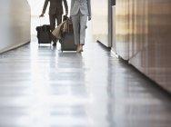 Unternehmer und Unternehmerin ziehen Koffer Rampe im Flughafen — Stockfoto