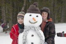 Portrait of happy boys posing with snowman — Stock Photo