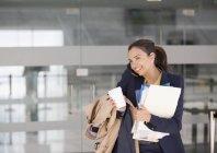 Mulher de negócios sorridente multitarefa no celular com café e papelada — Fotografia de Stock