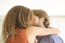 Joven atractiva pareja besándose en el interior - foto de stock