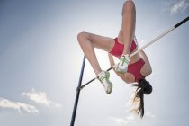 High jumper clearing bar — Stock Photo