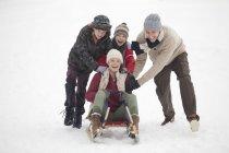 Happy family sledding in snow — Stock Photo