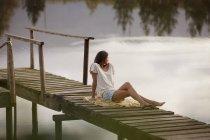 Женщина сидит на причале над озером — стоковое фото