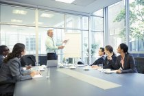 Businessman leading meeting at flipchart in conference room at modern office — Stock Photo