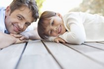 Father and daughter laying on porch — Stockfoto
