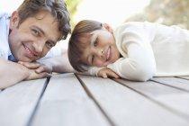 Отец и дочь лежат на крыльце — стоковое фото