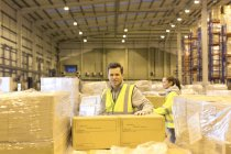 Работник распаковки коробки на складе — стоковое фото
