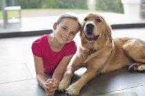 Lächelndes Mädchen mit Hund drinnen entspannen — Stockfoto