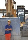 Worker standing by digger on site — Stock Photo
