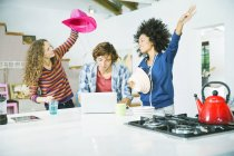 Young happy friends playing in kitchen — Stock Photo