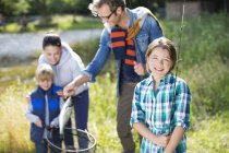 Family admiring fishing catch outdoors — Stock Photo