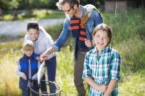 Famille admirant les captures de la pêche à l'extérieur — Photo de stock