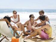 Heureux amis caucasiens traîner sur la plage — Photo de stock