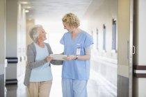 Enfermeira e paciente idoso conversando no corredor hospitalar — Fotografia de Stock