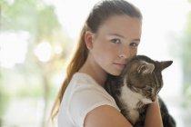 Девушка держит кота на размытом фоне — стоковое фото