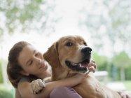 Lächelnde Mädchen umarmt Hund im freien — Stockfoto