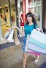 Donna portando borse shopping in via della città — Foto stock