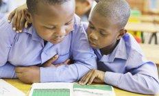 Estudiantes afroamericanos leyendo juntos en clase - foto de stock