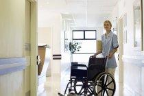 Enfermeira empurrando cadeira de rodas no corredor do hospital — Fotografia de Stock