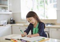 Girl using coloring book in kitchen — Stockfoto