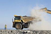 Travailleurs surveillant pelleteuse et camion dans la carrière — Photo de stock