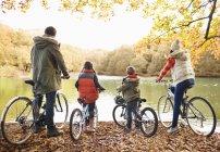 Vista traseira da família sentada em bicicletas juntos no parque — Fotografia de Stock
