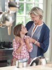 Woman and granddaughter smiling in kitchen — Stock Photo