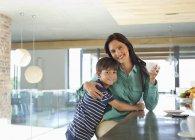 Madre e hijo sonriendo en cocina - foto de stock