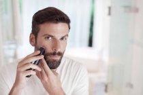 Man trimming beard in bathroom mirror — Stock Photo