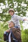 Uomo che trasporta la nipote sulle spalle all'aperto — Foto stock