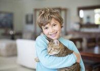 Кавказский мальчик обнимает кота в гостиной — стоковое фото