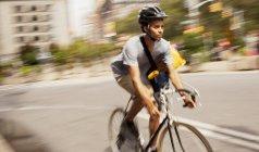Человек в шлеме катается на велосипеде по городской улице — стоковое фото