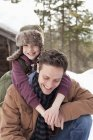 Portrait of happy son hugging father in snow — Stock Photo
