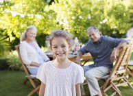 Girl smiling in backyard with grandparents — Stock Photo