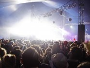 Fans facing illuminated stage at music festival — Stock Photo