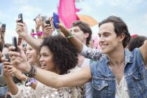 Fans with camera phones cheering at music festival — Stock Photo