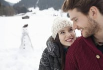 Close up of happy couple in snowy field with snowman — Stock Photo