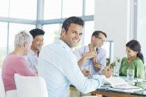 Бизнесмен улыбается на обеденной встрече в современном офисе — стоковое фото