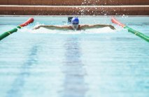 Swimmer racing in pool water — Stock Photo