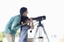 Mother and son using telescope — Stock Photo