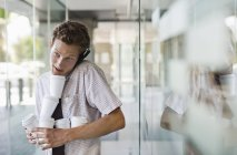 Empresário equilibrando cafés no escritório moderno — Fotografia de Stock