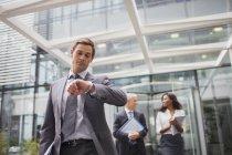 Homme d'affaires regardant la montre sortir de l'immeuble de bureaux — Photo de stock