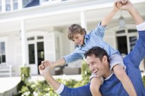 Father and son playing outside house — Stock Photo