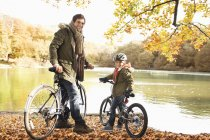 Father and son sitting on bicycles in park — Stock Photo